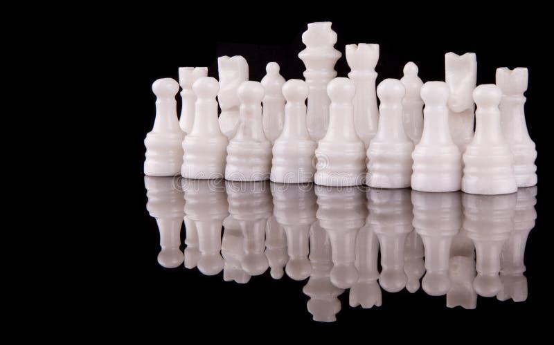 White Stone Made Chess Set II. White pieces of stone made chess set on black background royalty free stock photo