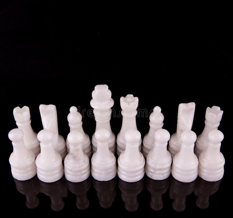 White Stone Made Chess Set III. White pieces of stone made chess set on black background royalty free stock photos