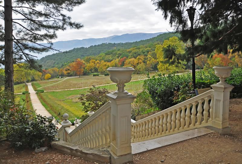 A white stone staircase in the autumn garden leads to the yellow autumn trees on a background of mountains with clouds stock photo
