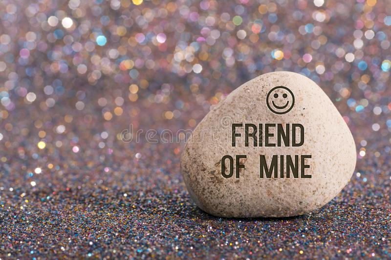 Friend of mine on stone. A white stone with words Friend of mine and smile face on color glitter boke background royalty free stock images