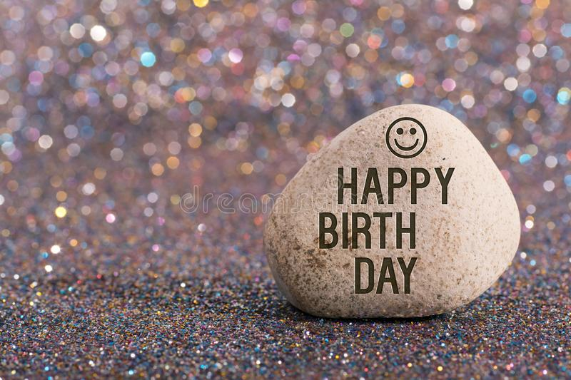 Happy birth day on stone. A white stone with words happy birth day and smile face on color glitter boke background royalty free stock image