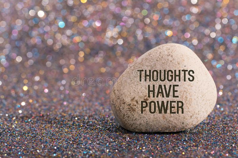 Thoughts have power on stone. A white stone with words thoughts have power and smile face on color glitter boke background royalty free stock photography