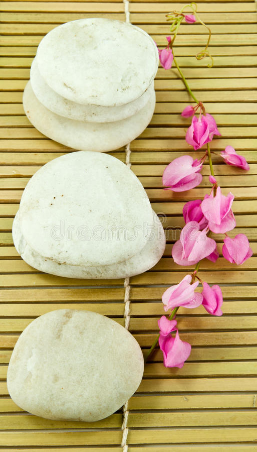 White stones with flower. A white stones with flower on bamboo royalty free stock photo