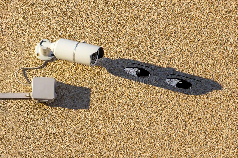 A white street videocamera with cable and a box hangs on a concrete wall and casts a shadow over which the eyes of a spying spy royalty free stock image