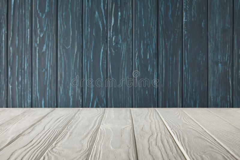 White striped tabletop and dark blue. Wooden wall royalty free stock images