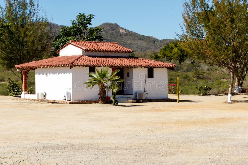 White stucco house with a red clay tile roof. White, stucco hacienda overlooking Lake Picachos in Sinaloa County, Mexico.  The reservoir is a famous sport stock photo