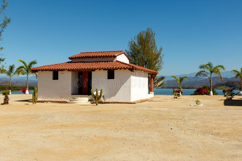 White stucco house with a red clay tile roof. White, stucco hacienda overlooking Lake Picachos in Sinaloa County, Mexico.  The reservoir is a famous sport stock images
