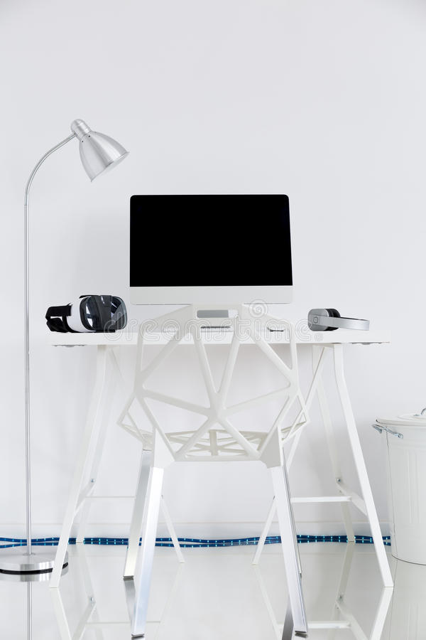 White study with a computer, a lamp and a gap chair. Shot of a white study with a computer, a lamp and a gap chair royalty free stock image