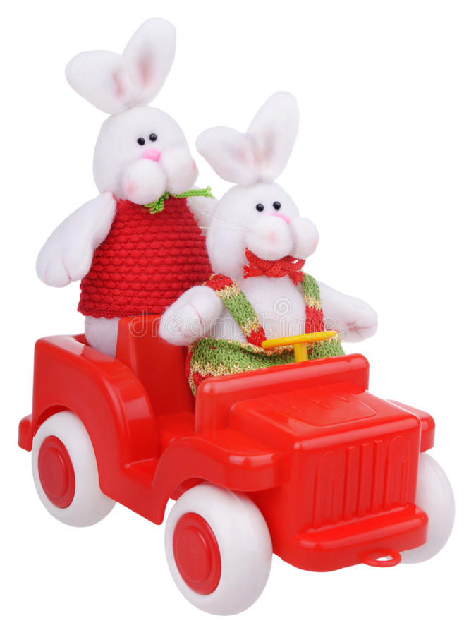 White stuffed rabbits in red car royalty free stock photography
