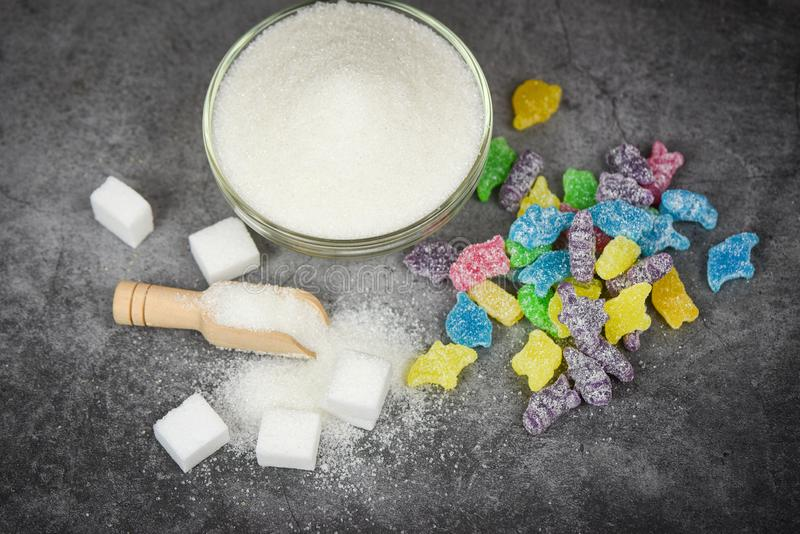 White sugar and colorful candy sweet on the dark table background / No sugar in diet causes obesity diabetes and other health stock photography