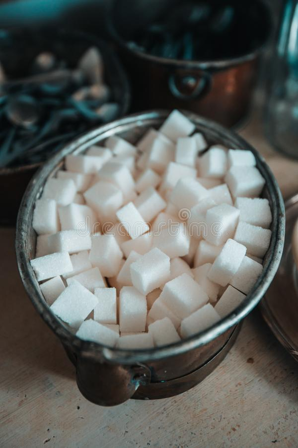 White sugar cubes on the black plate with sugar tongs. Metal vintage asian teapot on the background. Closeup, selective focus,. White sugar cubes on the black royalty free stock photography