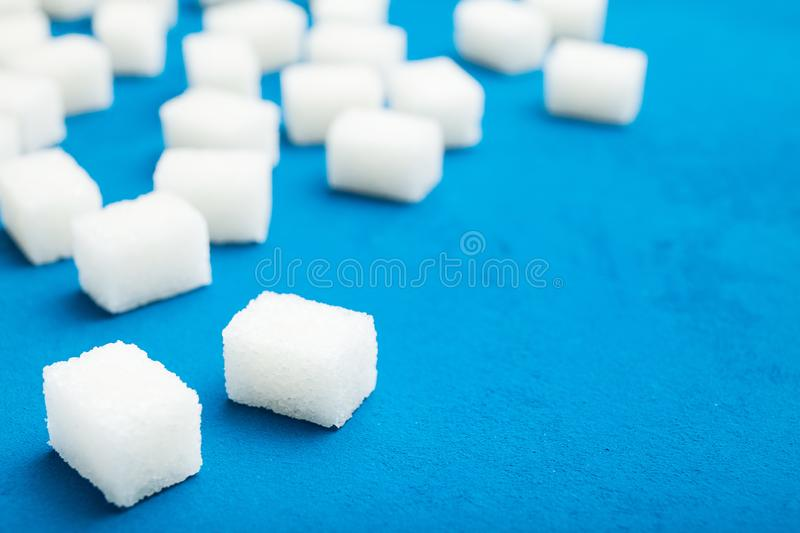 White sugar cubes on a blue vintage background. Copy space.  stock photography