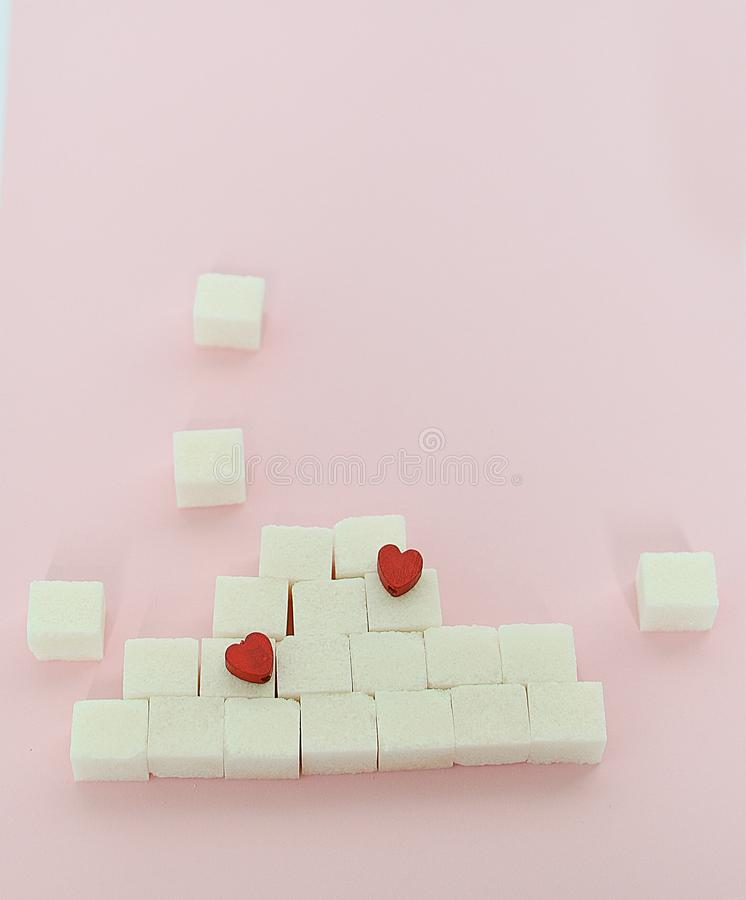 White sugar cubes on a pink background. What are the concepts of diabetes and calorie intake The concept of heart disease. No royalty free stock photo