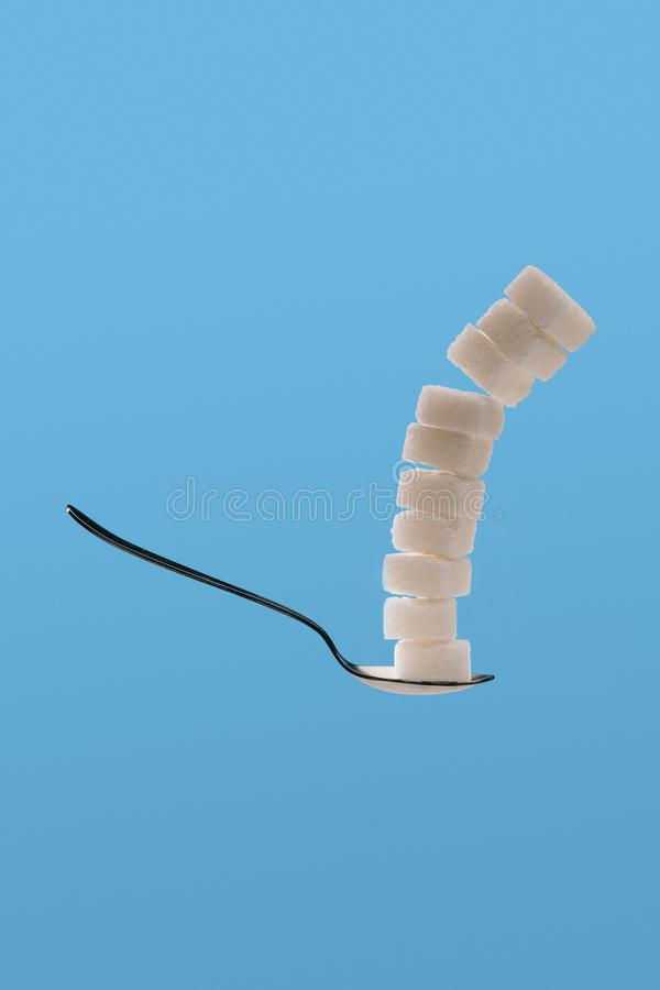 White sugar cubes in spoon. Isolated on blue background stock photography
