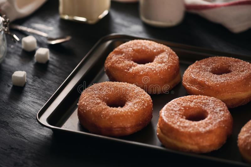 White sugar donuts on a sheet metal tray.  royalty free stock photography