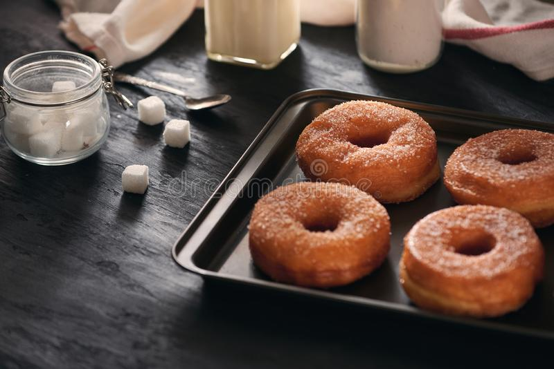 White sugar donuts on a sheet metal tray royalty free stock images