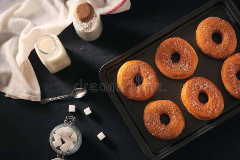 White sugar donuts on a sheet metal tray.  stock photo
