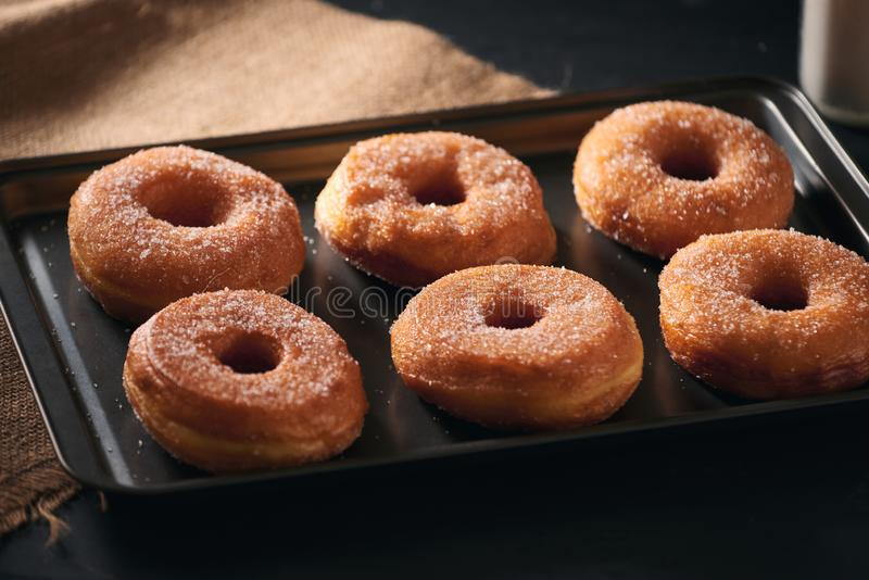 White sugar donuts on a sheet metal tray.  stock images