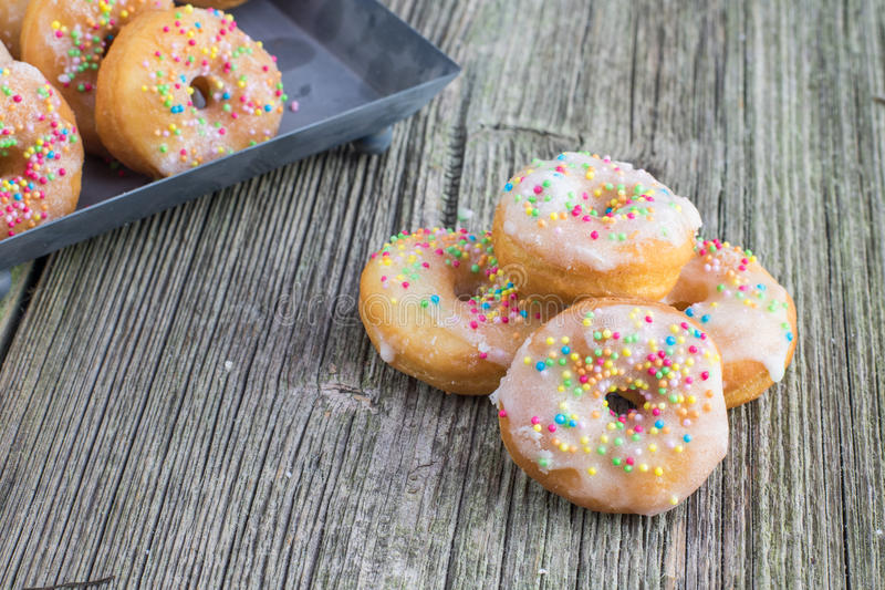 White sugar glazed mini donuts on old wooden board stock photography