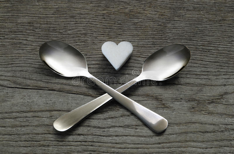 White sugar heart with two crossed spoons, unhealthy concept stock images