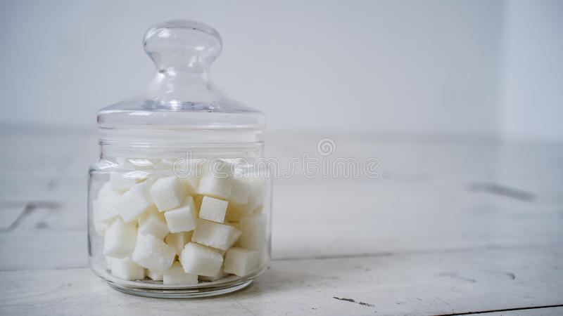 White sugar lumps in a glass jar on the wooden table painted in royalty free stock photo