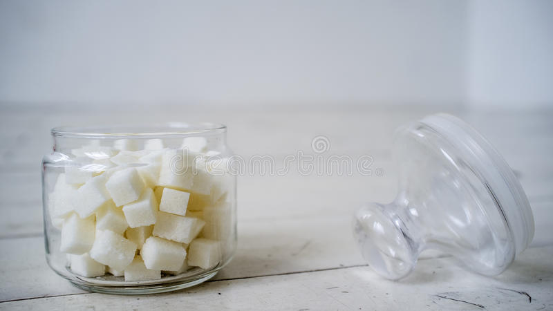 White sugar lumps in a glass jar on the wooden table painted in stock image