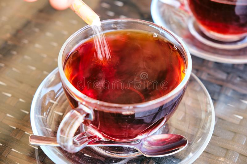 Sugar poured in traditional turkish tea in glass. White sugar poured in traditional turkish tea in clear glass stock image