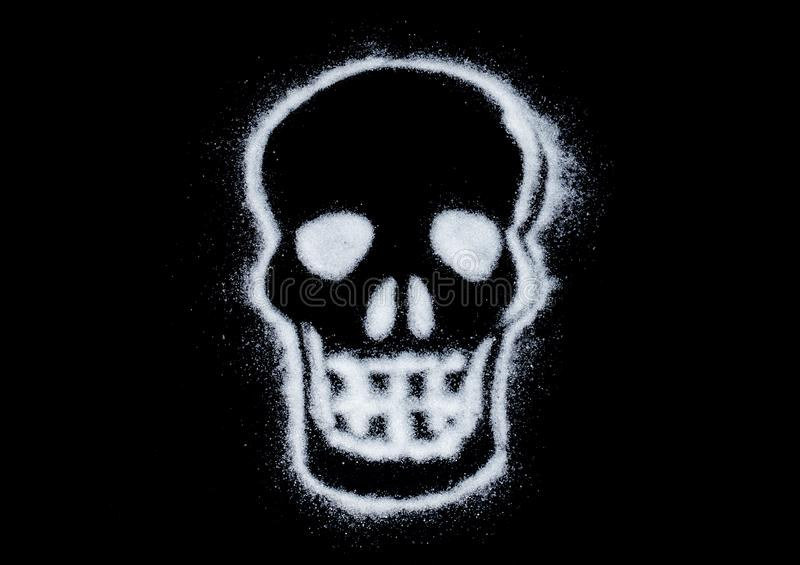 White sugar in shape of the skull on black background. caution sign. deadly addiction royalty free stock photography