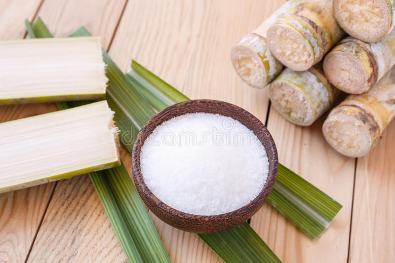 White sugar and sugar cane on wooden table background stock photos