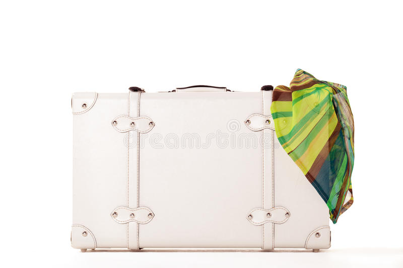 White suitcase on white bacground. White suitcase on white background, standing on white surface with dress sticked out stock photo