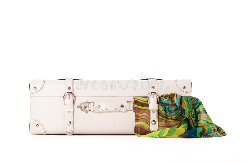 White suitcase on white bacground. White suitcase on white background, standing on white surface with dress sticked out stock images