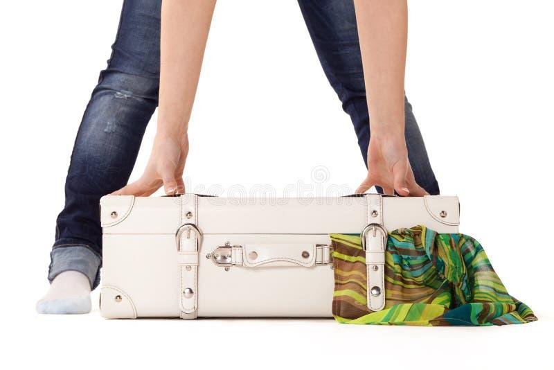 White suitcase on white bacground. White suitcase on white background, standing on white surface with dress sticked out royalty free stock photos