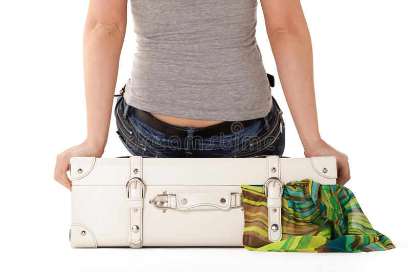 White suitcase on white bacground. White suitcase on white background, standing on white surface with dress sticked out royalty free stock image