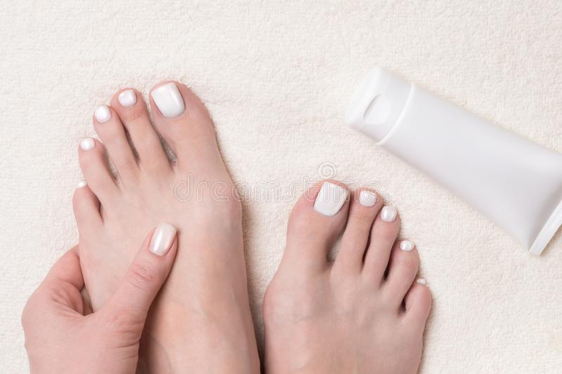 White summer pedicure. Female bare feet, toes close up and tube of cream on ivory terry towel. Spa, organic, treatment, beauty shop, massage and skin care stock photography