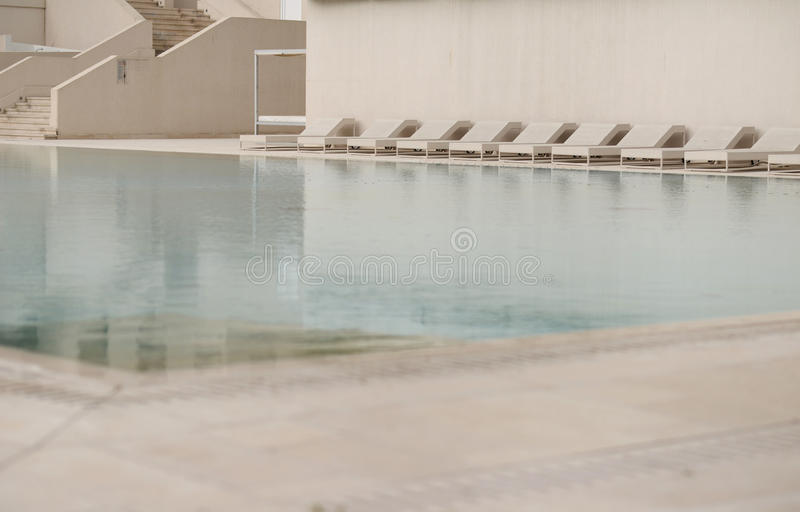 White sun loungers and deckchairs next to the swimming - Waterford crystal swimming pool times ...