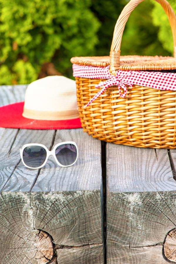 White sunglasses summer hat and wicker basket on wooden table stock image
