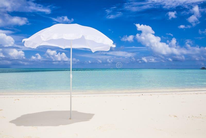white sunshade at the beach stock photo