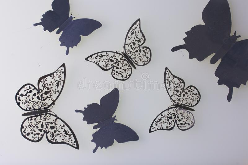 On the white surface lie decorations made of butterflies cut from foil. royalty free stock photo