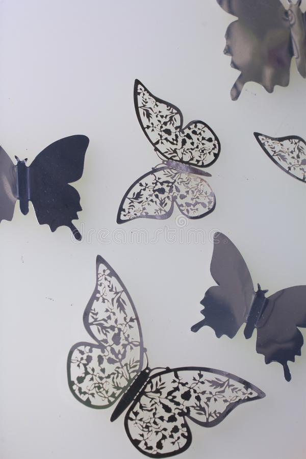On the white surface lie decorations made of butterflies cut from foil. stock photo