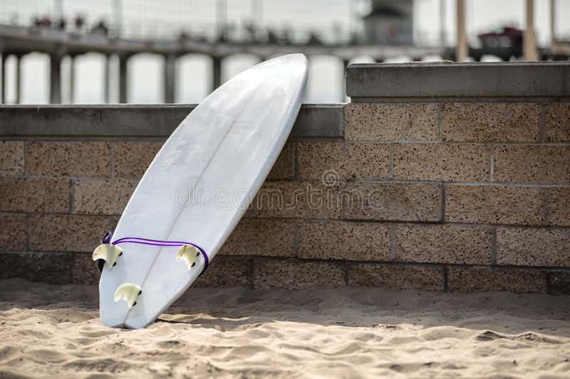 White surfboard leaning on the stone wall. On the beach stock photography