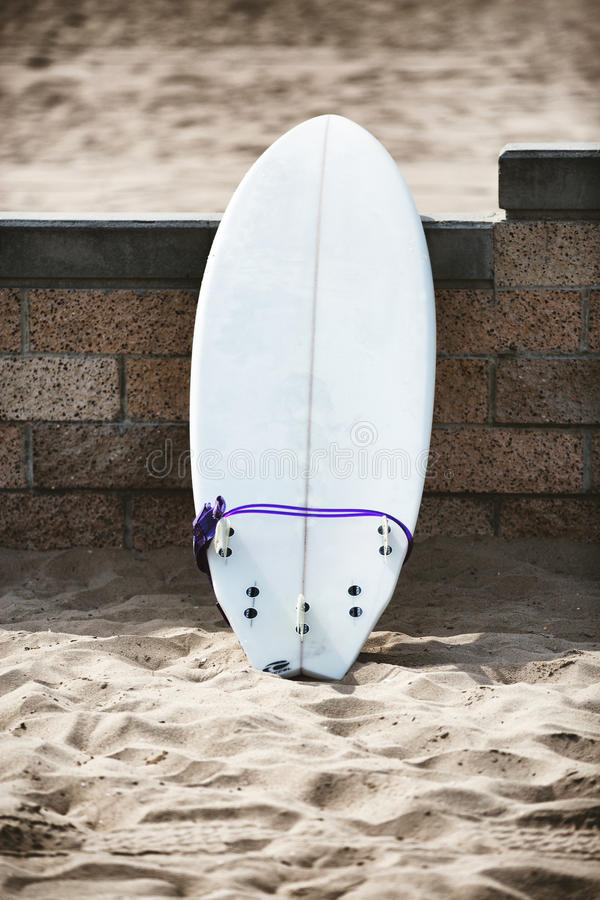 White surfboard leaning on the stone wall. On the beach royalty free stock image
