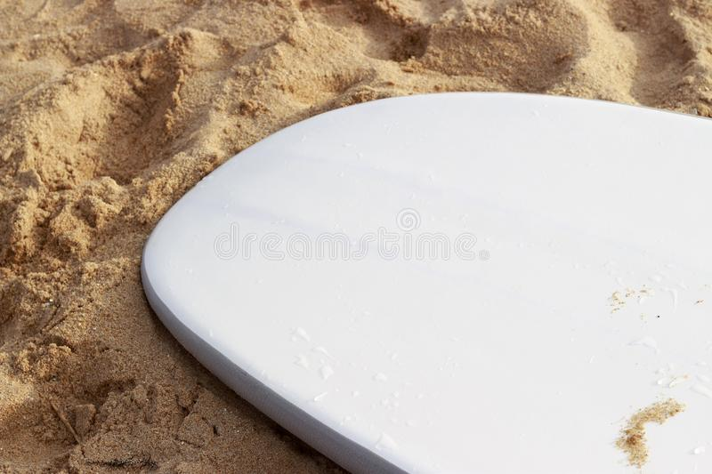 White surfboard lying on the sand close-up side view stock images