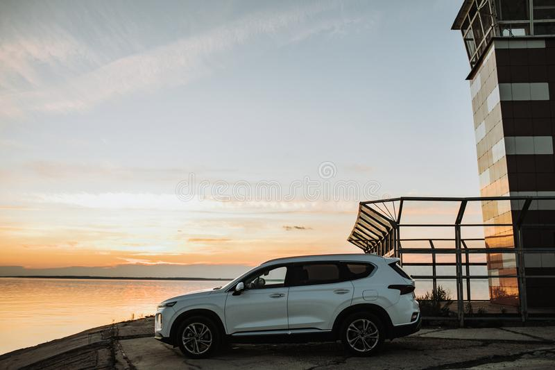 White compact SUV car with sport and modern design parked on concrete road by the sea near the beach at sunset royalty free stock photos
