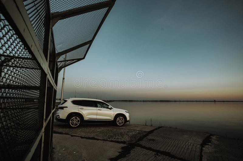 White compact SUV car with sport and modern design parked on concrete road by the sea near the beach at sunset stock image
