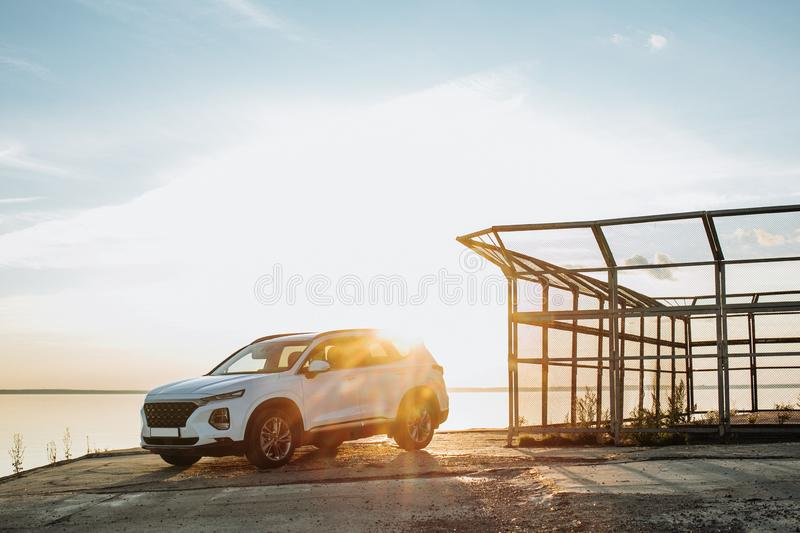 White compact SUV car with sport and modern design parked on concrete road by the sea near the beach at sunset royalty free stock photography