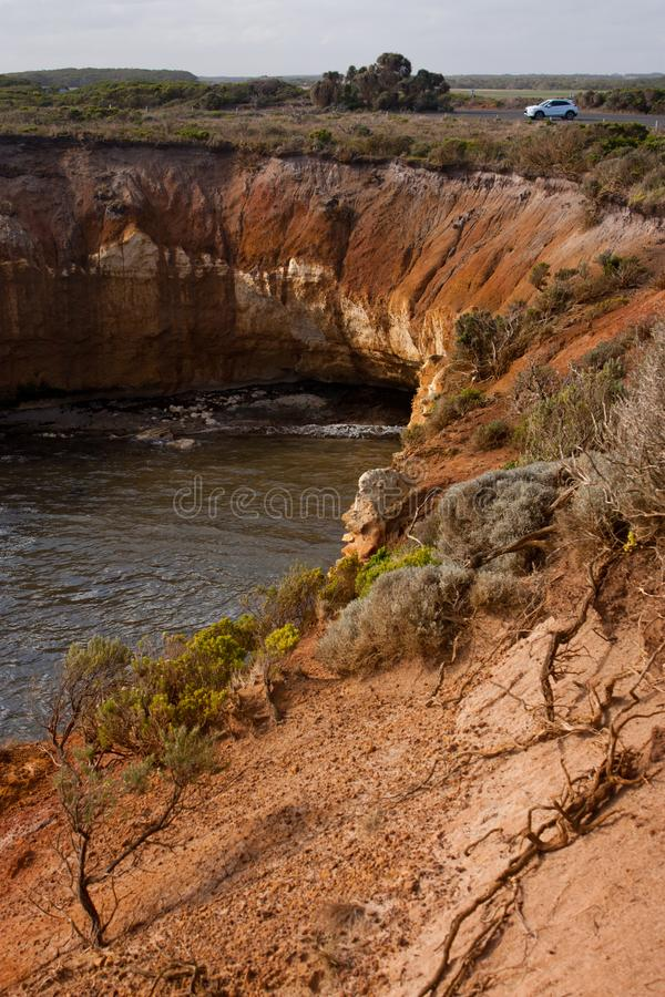 A white SUV car at the top of a sandstone cliff at the Bay of Islands on the Great Ocean Road in Australia. A white SUV car at the top of a sandstone cliff at stock images
