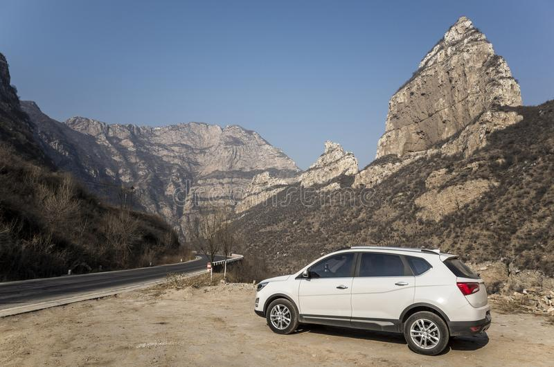 White SUV in the mountain road. The white SUV leaned against the mountain road in winter stock photos