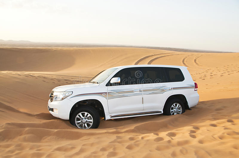 White SUV Toyota Land Cruiser in desert royalty free stock image