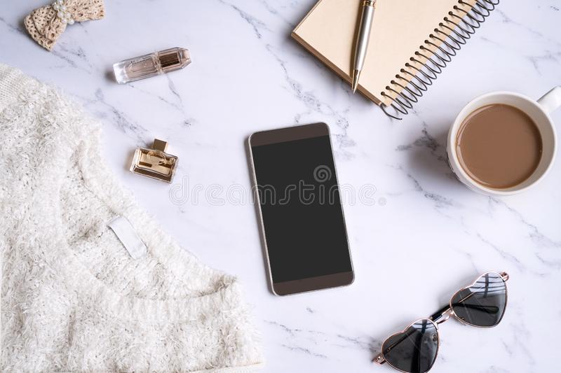 White sweater, women accessories,coffee ,notebook, smart phone on marble background. Women clothing. Flat lay royalty free stock images
