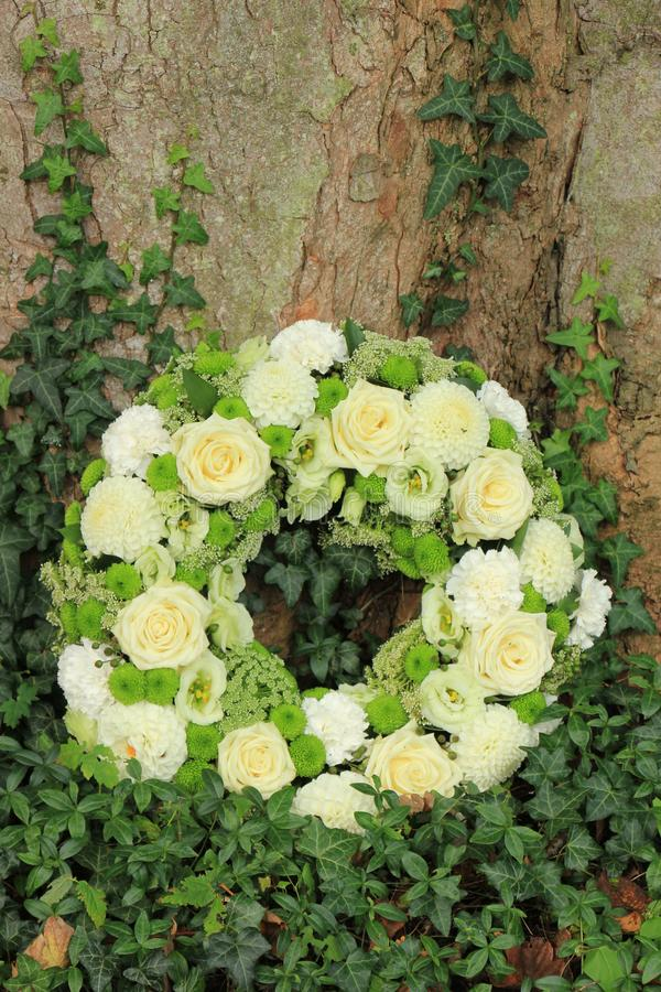 White sympathy wreath near a tree. White sympathy wreath or funeral flowers near a tree, white roses and mums royalty free stock photos